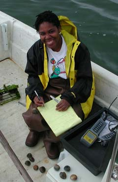 Former masters student, Ayana McCoy (MS  2005),  records water quality measurements at a sampling site near Cedar Key, Florida. (photo by D. Bergquist)